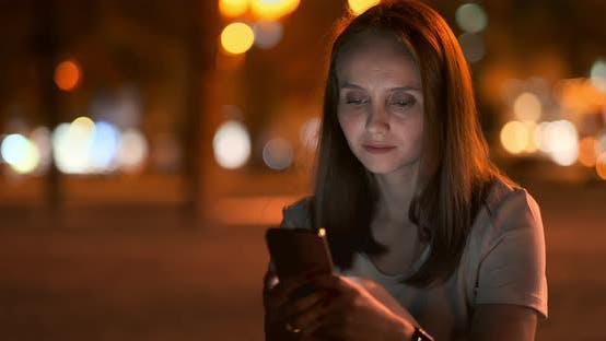 Cover Image for Young Girl in the Night City Writes Text Messages in a Smartphone