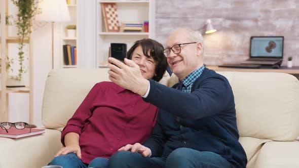 Thumbnail for Happy Senior Couple Sitting on Sofa Taking a Selfie