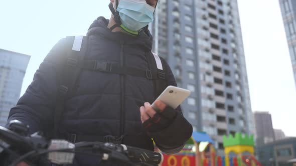 Delivery Man in Face Mask Taking Order on Phone
