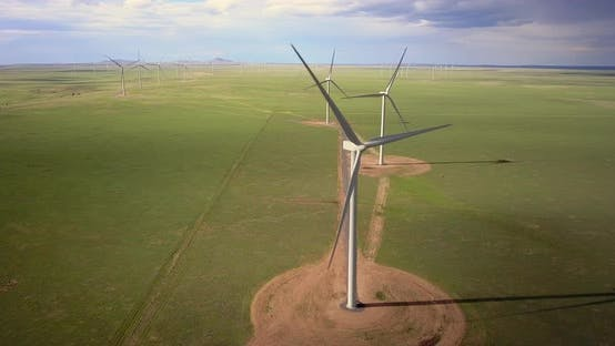 Aerial of wind turbine blades rotating in the wind farm, wide shot