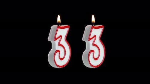 Candle in the Shape of the Number Thirty Three on a Black Background