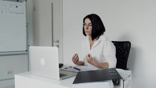 Female Teacher in Glasses Chatting on a Laptop During Remote Learning in Office