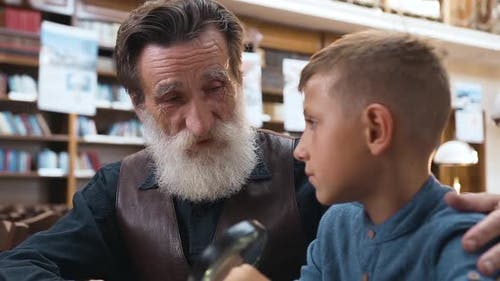 Teen Schoolboy Carefully Listening His Senior Respected Grandfather Telling about Books