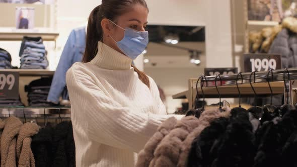 Slim Lady in Face Mask Chooses Size of Brown Winter Coat