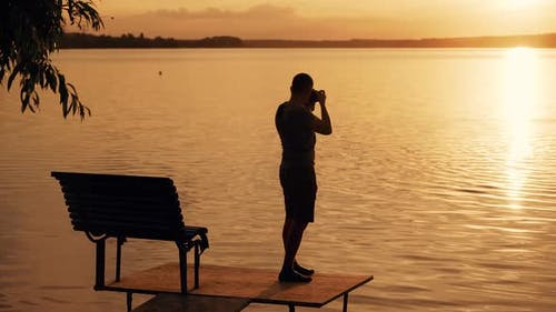 A talented photographer with a camera in his hands taking pictures of the sunset on the river