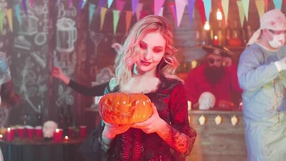 Sexy Vampirin mit einem Jack-o-Laterne in Ihren Händen bei einer Halloween-Party