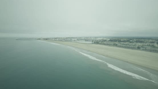 Thumbnail for Camera pan from oceanside homes onto water, helicopter aerial daytime shot