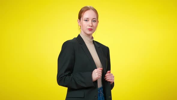 Middle Shot of Confident Sensual Young Businesswoman in Suit Flirting with Camera at Yellow