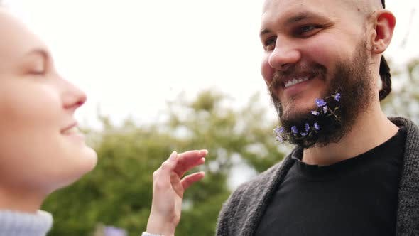Thumbnail for The Man with a Violet Flower on His Beard Is Looking at a Woman and Smiling