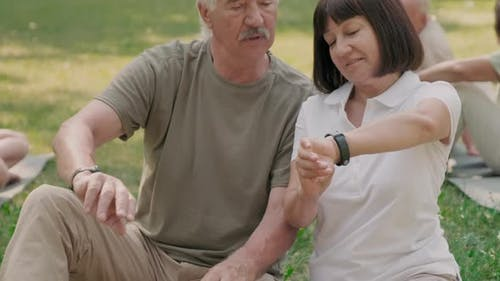 Aged Man and Woman Using Their Smartwatches Outdoors