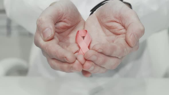 Breast Cancer Awareness Pink Ribbon in the Hands of a Doctor