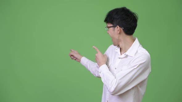 Thumbnail for Young Happy Asian Businessman Pointing To the Back