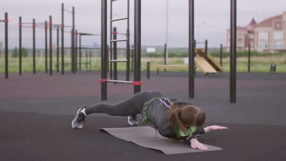 Thumbnail for Athletic Woman Performing Side Plank Reverse Fly during Outdoor Workout