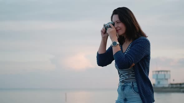 Thumbnail for Young Woman Takes Pictures on a Vintage Camera By the Ocean. Portrait of a Girl with a Retro Camera