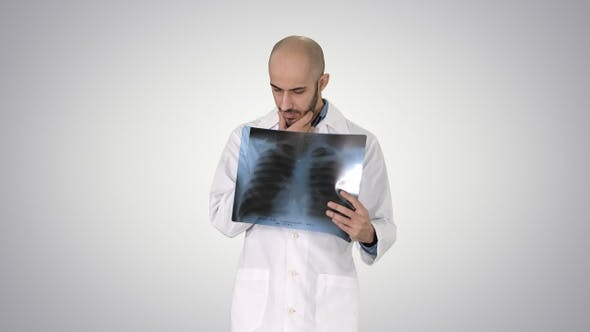 Thumbnail for Doctor radiologist looking at x-ray scan walking on gradient