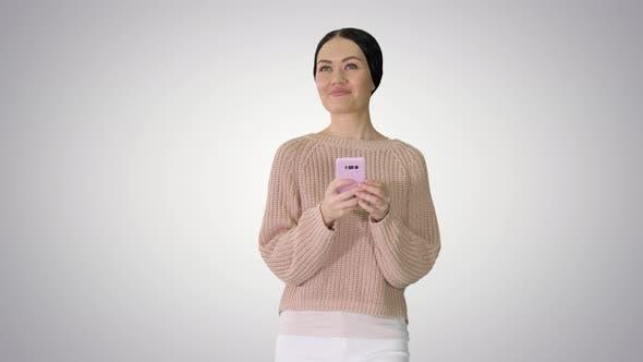 Hübsche junge weibliche SMS auf Handy beim Gehen auf Farbverlauf Hintergrund.