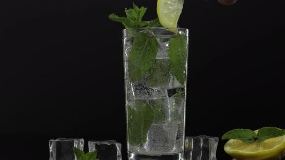 Thumbnail for Clear Water in Glass with Green Mint Leaves and Ice Cubes on Black Background