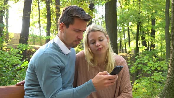 Thumbnail for A Young Attractive Couple Looks at a Smartphone on a Bench in a Park on a Sunny Day - Closeup