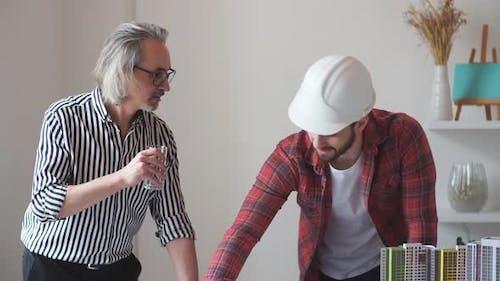 Mature, architecte senior partage ses connaissances avec Guy.