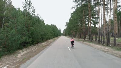 Cyclist cycling in cycling apparel and helmet on bicycle. Cycling in forest.