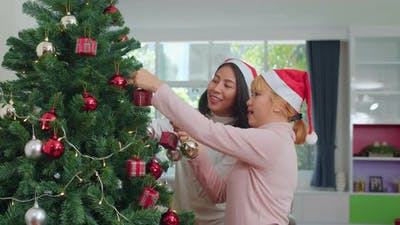 Asian women friends decorate Christmas tree at Christmas festival in living room at home.