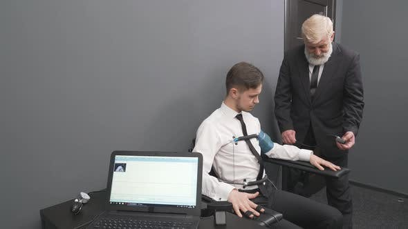Thumbnail for Aged Man Attaching Sensors on Fingers and Body To Young Guy