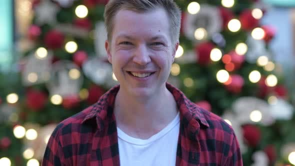 Cover Image for Happy Young Handsome Man Against Illuminated Christmas Trees Outdoors