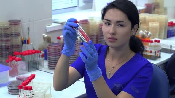 Thumbnail for Young Woman in Blue Uniform Taking Two Tubes From a Rack for Test Tubes and Checking Color and