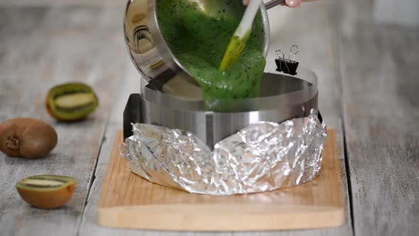 Thumbnail for Pastry chef making a kiwi mousse cake on kitchen. Pouring kiwi jelly on top the cake.