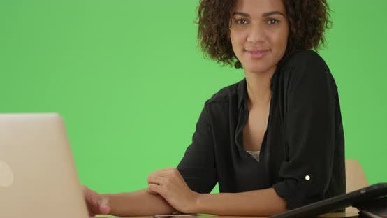Thumbnail for Millennial black woman looks at the camera at her desk on green screen