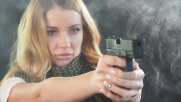 Thumbnail for Armed Blonde Woman Shoots with Gun at a Target in the Darkness with Smoke Clouds
