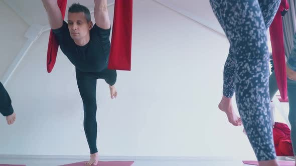 Thumbnail for Concentrated Man and Ladies Practice Anti-gravity Yoga