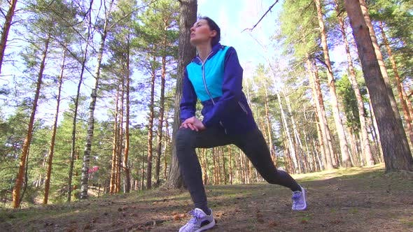 Sports Girl Brunette Stretching in a Sunny Forestslow Mo