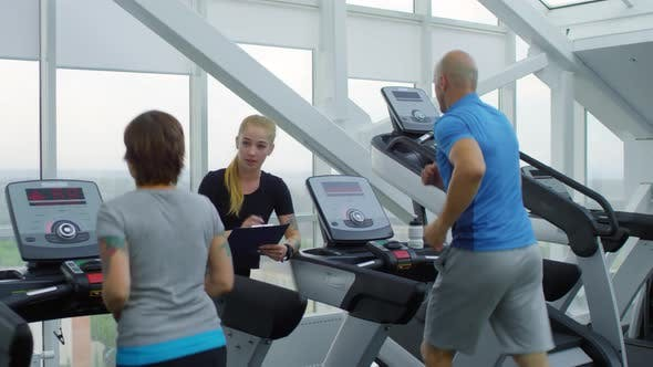 Thumbnail for Trainer Talking to Man and Woman in Gym