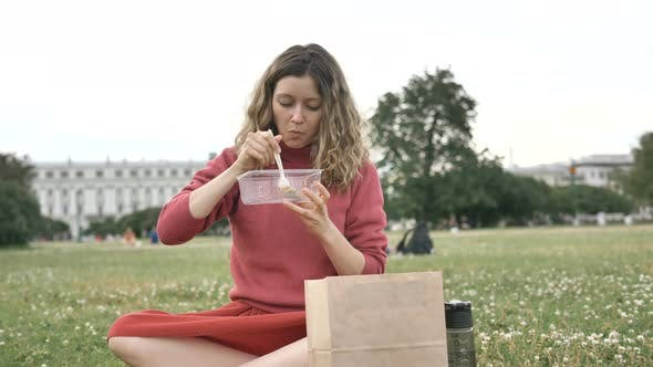 Thumbnail for Girl Eats Food of Their Disposable Container Sitting on the Grass in the Park