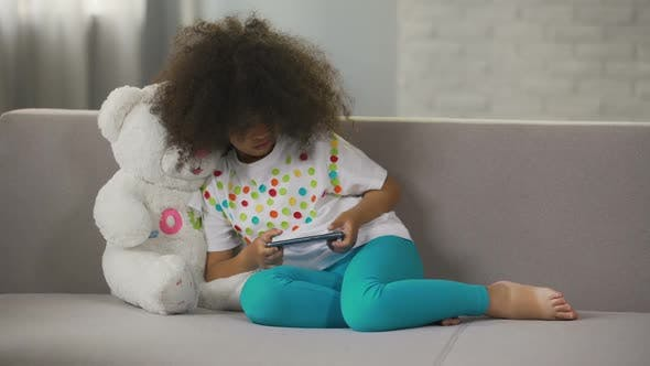 Thumbnail for Little African American Girl Sitting on Couch and Playing Game on Cellphone