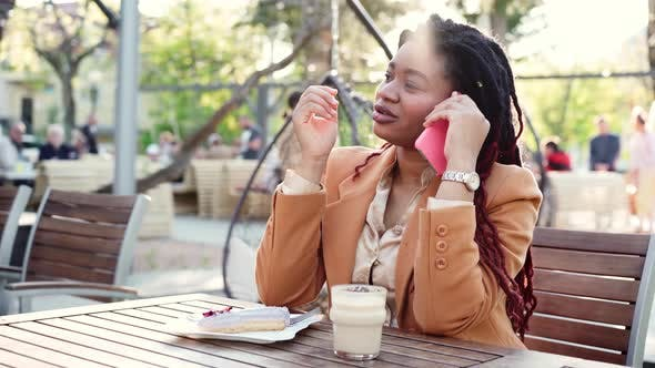 African American Woman Sitting in Outdoor Cafe and Talking on the Phone