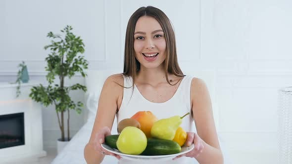 Cover Image for Attractive Caucasian Woman Stretching Out Plate With Fruits to the Camera