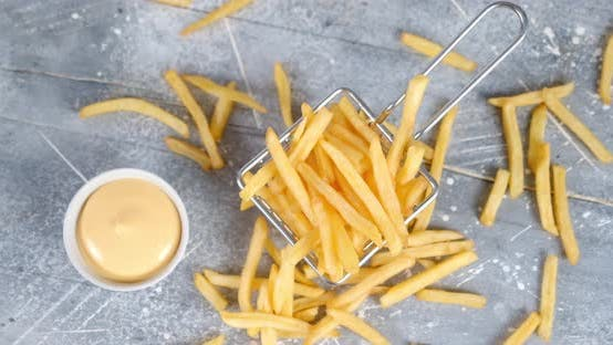 French Fries in a Basket with a Sauce Slowly Rotates.