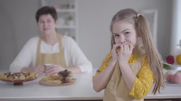 Cover Image for Portrait of Cute Little Girl Eating Pancake with Blurred Caucasian Grandmother Smiling at the