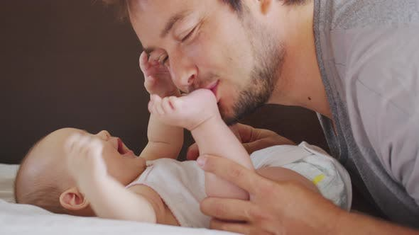 Thumbnail for Close of Millennial Black Father Lying on Bed Playing with His Newborn Baby Dauther.