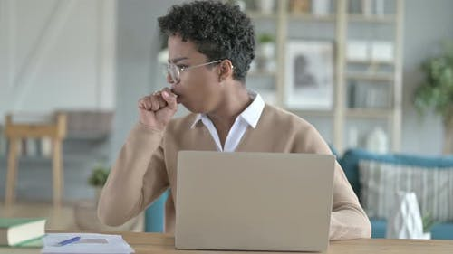 Working African Girl Coughing While Using Laptop