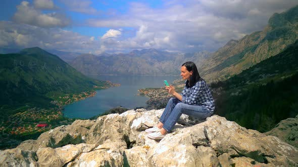 Cover Image for Middle-Aged Woman Sitting on Top of Mountain and Talking By Smartphone