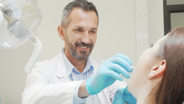 Thumbnail for Experienced Male Dentist Smiling While Checking Teeth of a Patient
