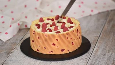 Cutting a Raspberry Mousse French Dessert