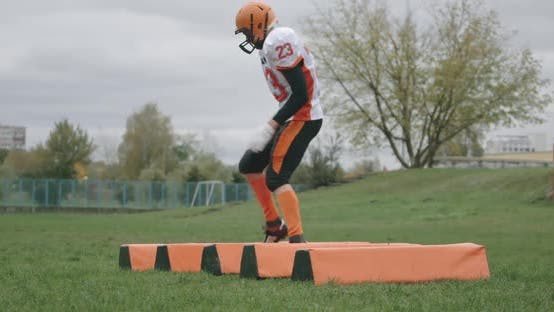American Football, Young Soccer Player in Protective Gear Jumps Over Obstacles, Coordination