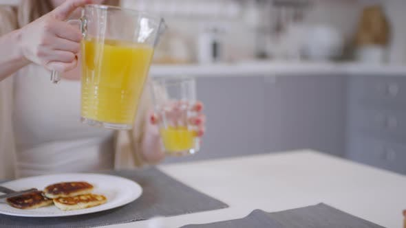 Thumbnail for Woman Pouring Orange Juice into Glass