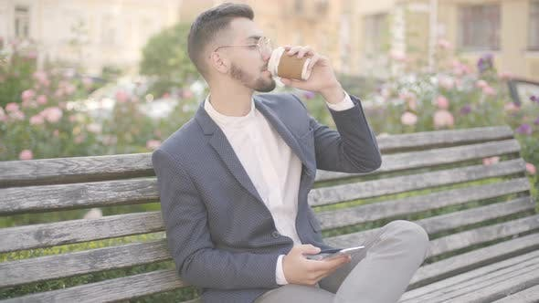 Cover Image for Portrait of Confident Young Businessman Sitting on a Bench Outdoors