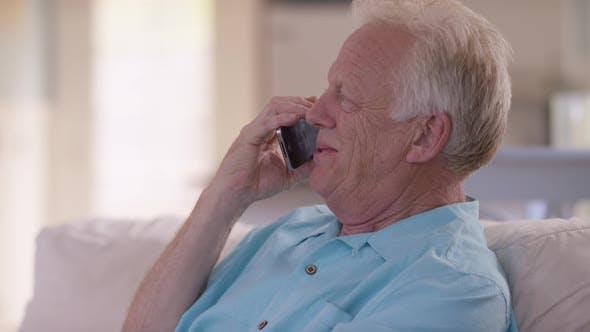 Thumbnail for Senior Mann im Wohnzimmer im Gespräch auf Handy