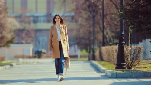Pretty Young Woman Walks Down the Street in a Coat